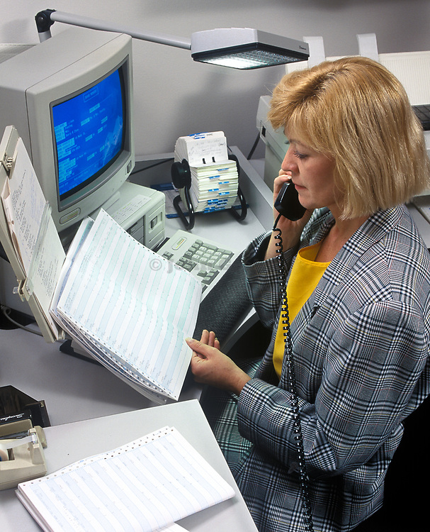 Businness woman with spreadsheet and computer talks on telephone.