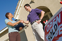 Man shaking hands with estate agent outside their new home