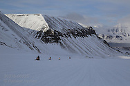 Snowmobilers speed up snow-covered glacier above Longyearbyen in April; Svalbard, Norway.