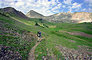 A hiker backpacks along a trail in the high country of Colorado