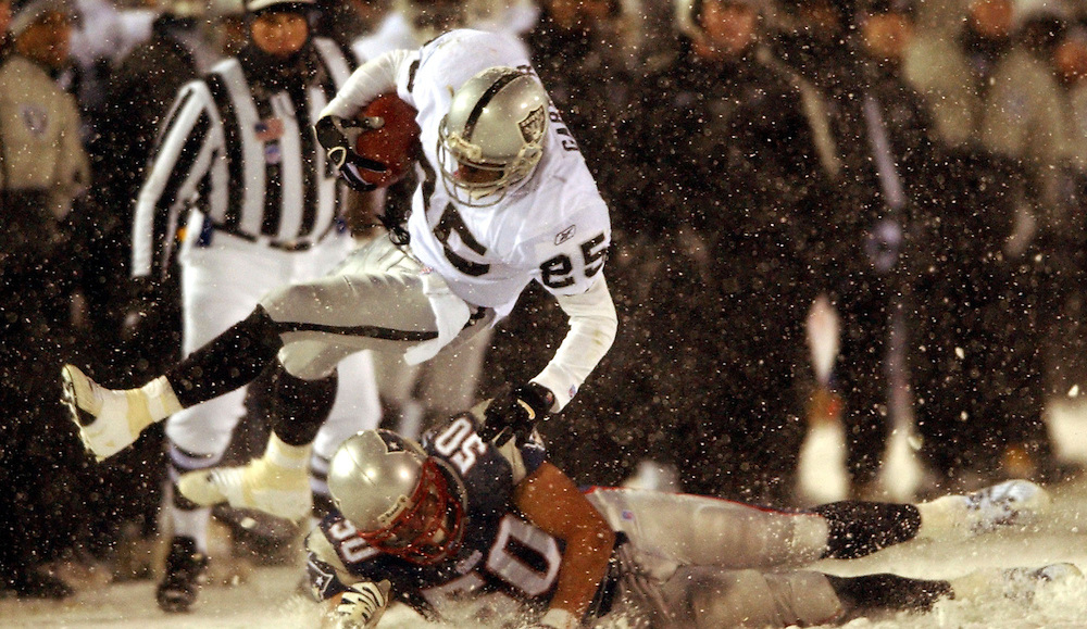 (1/19/02 Foxboro, MA) Patriots vs. Raiders at Foxboro Stadium. Raiders (25) Charles Garner goes up and over Pats (50) Mike Vrabel in the second quarter. (011902patsMJS13.jpg- Staff Photo by Michael Seamans. Saved in Sunday/FTP)