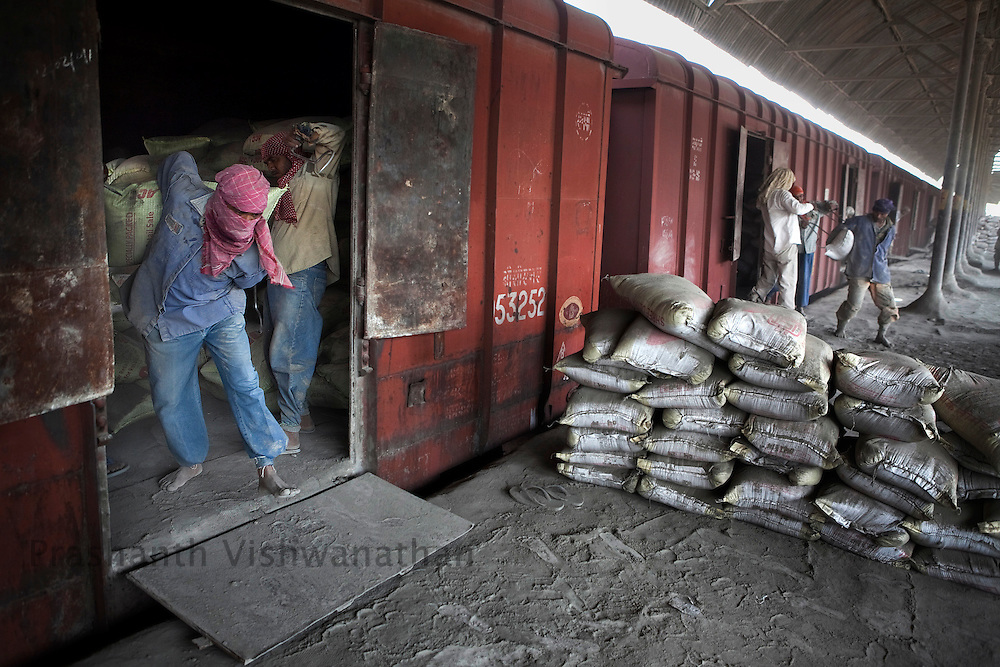 Labourers unload cement bags from freight trains manually at the Shakur Basti station in New Delhi, India, on Tuesday April 5, 2011.  Photographer: Prashanth Vishwanathan/Bloomberg News