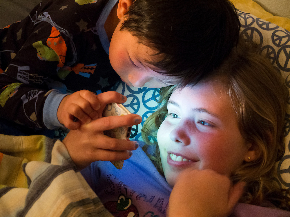 With their faces illuminated by the glow of an electronic video device, Holden Miller, 4, and his cousin, Rachel Stute, 11, have a hard time settling down for bed during Rachel's visit and sleepover at the Miller/Stute home in Madison, Wis., on April 27, 2012.