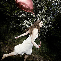 A young old girl running down a country lane holding a red ballon shaped like a heart, wearing a white dress.