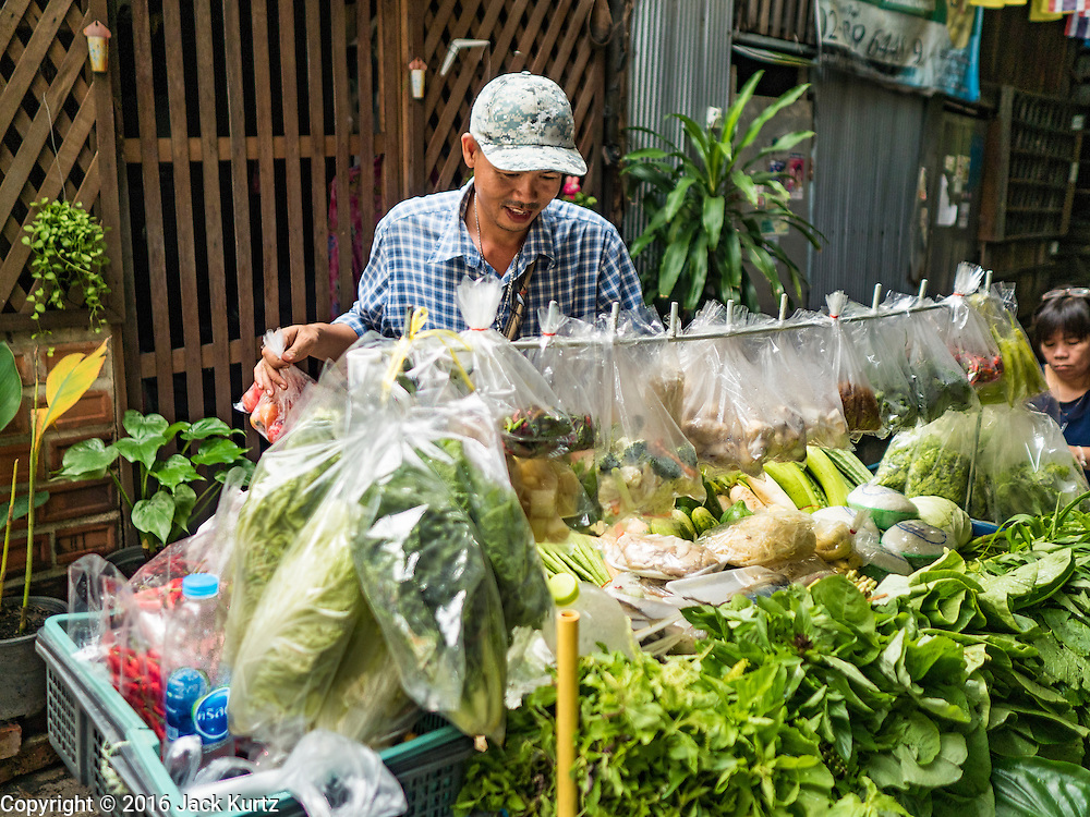 10 AUGUST 2016 - BANGKOK, THAILAND: A produce vendor who sells in the Pom Mahakan slum selects vegetables for a customer. Residents of the slum have been told they must leave the fort and that their community will be torn down. The community is known for fireworks, fighting cocks and bird cages. Mahakan Fort was built in 1783 during the reign of Siamese King Rama I. It was one of 14 fortresses designed to protect Bangkok from foreign invaders. Only of two are remaining, the others have been torn down. A community developed in the fort when people started building houses and moving into it during the reign of King Rama V (1868-1910). The land was expropriated by Bangkok city government in 1992, but the people living in the fort refused to move. In 2004 courts ruled against the residents and said the city could take the land. Eviction notices have been posted in the community but most residents have refused to move. Residents think Bangkok city officials will start evictions around August 15, but there has not been any official word from the city.       PHOTO BY JACK KURTZ