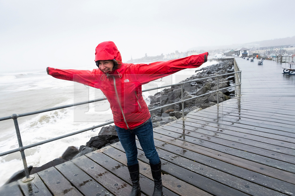 © Licensed to London News Pictures. 16/03/2019. Aberystwyth, UK.  A woman in a red raincoat struggles to walk as Storm Hannah brings huge waves crashing into the harbour lighthouse and sea defences on an extremely wet and windy day in Aberystwyth Wales.  Gusts of over 50mph are forecast to impact parts of the north and west of the country today as the period of very unsettled weather  continues to dominate the UK. Photo credit: Keith Morris/LNP