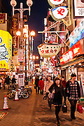 Pedestrians walk under neon and extreme signage in Dotonburi.