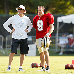 July 29, 2012; Metairie, LA, USA; New Orleans Saints general manager Mickey Loomis talks with quarterback Drew Brees (9) during a training camp practice at the team's practice facility. Mandatory Credit: Derick E. Hingle-US PRESSWIRE