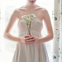 Slender girl wearing a white dress with pale skin holding baby's breath flowers, against a window with rain drops on it surrounded by floral curtains.