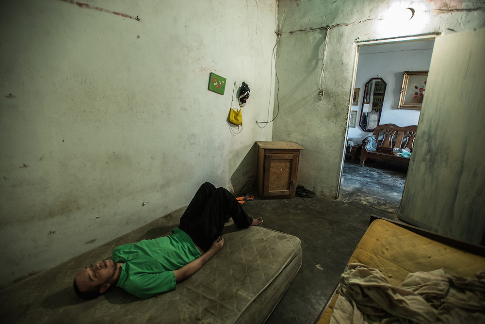 "MARACAY, VENEZUELA - JULY 4, 2016: Schizophrenic Gerardo Simeone rests on a mattress in his bedroom in the middle of the day.  He spends most of his days either sleeping, or standing in a corner in silence in his family's living room, rarely even making eye contact with members of his family.  His parents remember how he used to be when he was younger…before he became ill - recalling how affectionate and talkative he was. ""He was so kind and loving,"" said his mother, Evelin.  Gerardo's brother Accel is also schizophrenic. Their parents spend hours each week searching pharmacies for the psychiatric drugs that thier sons need, which are very difficult to find, because of nationwide shortages.  ""I am tired,"" Evelin said. ""This is too much sometimes"".  PHOTO: Meridith Kohut for The New York Times"