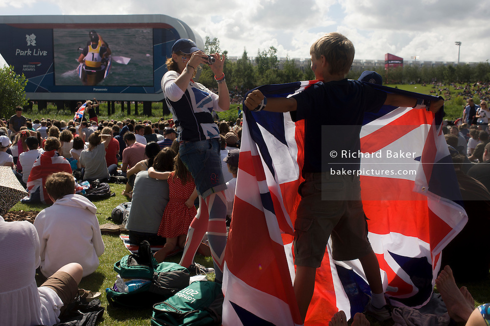The Team GB canoe slalom pair David Florence and Richard Hounslow celebrate after their C2 final race watched by celebrating fans in the Olympic Park during the London 2012 Olympics. This land was transformed to become a 2.5 Sq Km sporting complex, once industrial businesses and now the venue of eight venues including the main arena, Aquatics Centre and Velodrome plus the athletes' Olympic Village. After the Olympics, the park is to be known as Queen Elizabeth Olympic Park.