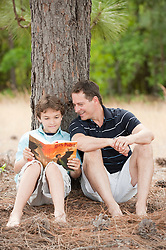 Man and Boy Reading A Book Together Under A Tree