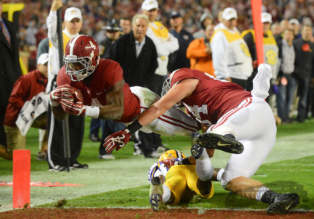 Photo by Gary Cosby Jr.  Alabama running back T.J. Yeldon dives into the end zone with a block on LSU cornerback Jalen Mills by Alabama tight end Brian Vogler during the latest game of the century between SEC West rivals Alabama and LSU in Bryant Denny Stadium.