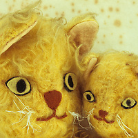 Heads of homemade glove puppets of mother or father cat with kitten with matted golden fur and tatty whiskers