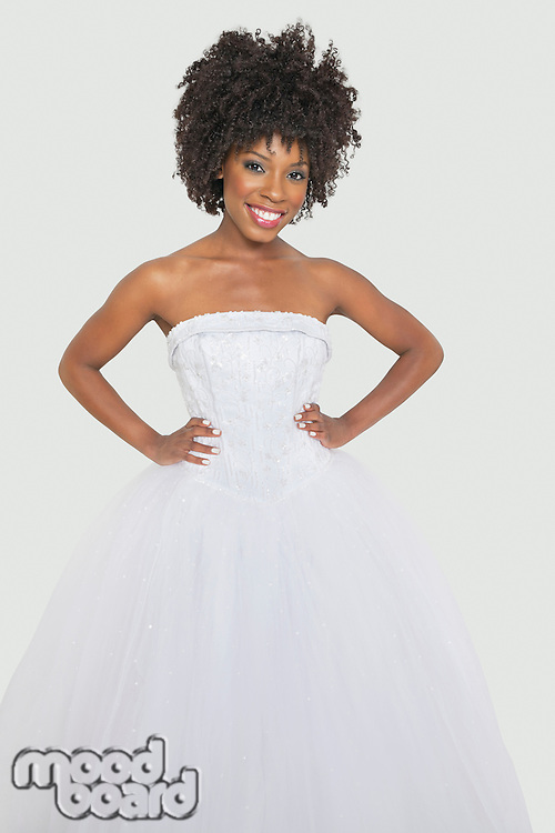 Portrait of pretty African American bride standing hands on hips against gray background