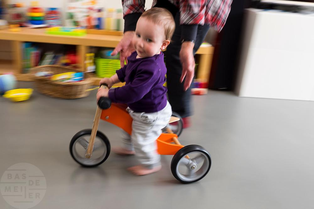In Utrecht rijdt een jongetje van 10 maanden op een houten loopfiets door de huiskamer. Een loopfiets wordt gezien als een goede opstap naar het fietsen.<br /> <br /> In Utrecht a boy of 10 months rides on a wooden balance bike through the living room. A balance bike is seen as a good stepping stone to cycling.