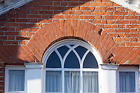 Domestic gothic window with Y tracery adorned by rubbed brick voussoirs to the window arch. Here in Lavenham, Suffolk, UK.