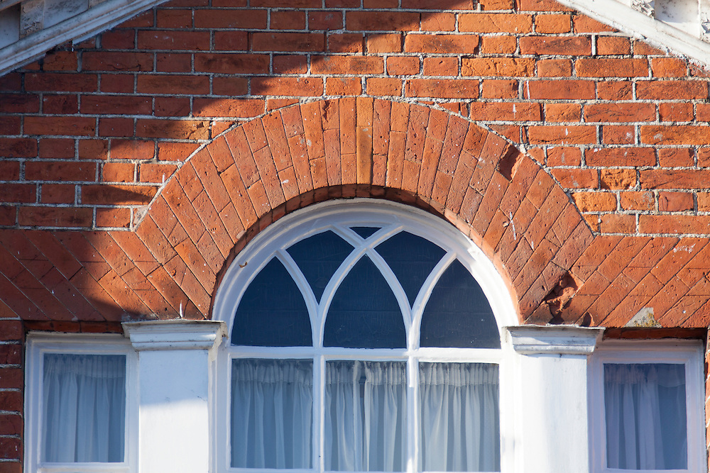 Domestic Gothic Window With Y Tracery Adorned By Rubbed Brick Voussoirs To The Arch