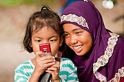 "Sept. 27, 2009 -- RANGAE, THAILAND: Muslim girls play with a cell phone camera near their family home in Rangae, Narathiwat, Thailand. Thailand's three southern most provinces; Yala, Pattani and Narathiwat are often called ""restive"" and a decades long Muslim insurgency has gained traction recently. Nearly 4,000 people have been killed since 2004. The three southern provinces are under emergency control and there are more than 60,000 Thai military, police and paramilitary militia forces trying to keep the peace battling insurgents who favor car bombs and assassination.   Photo by Jack Kurtz"