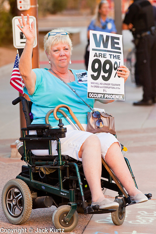 16 OCTOBER 2011 - PHOENIX, AZ: An Occupy Phoenix protester in a wheelchair waves to passing cars in downtown Phoenix, AZ, Sunday. About 200 people continued the Occupy Phoenix protest in downtown Phoenix Sunday afternoon. The protest peaked Saturday afternoon at about 2,000 people. Nearly 50 people were arrested late Saturday night on misdemeanor trespassing charges when they tried to camp in a park near downtown and on Sunday the crowd dwindled to 200. Protesters hope to continue the protest through Monday by marching around downtown and picketing banks in the area.    PHOTO BY JACK KURTZ