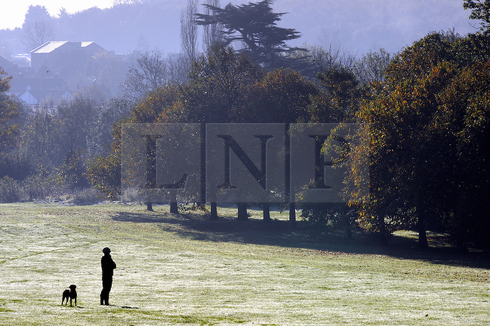 © Licensed to London News Pictures. 06/11/2014<br /> A dog walker just stands and looks at the view.<br /> Freezing cold weather and a cold mist over the River Cray this morning at Foots Cray Meadows,Sidcup,Kent.<br /> (Byline:Grant Falvey/LNP)