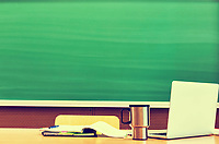 Photo of laptop on professor desk with tumbler and book against black board in classroom