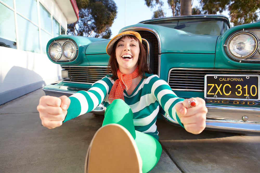 Lifestyle image of girl pretend driving in front of vintage green car in Southern California
