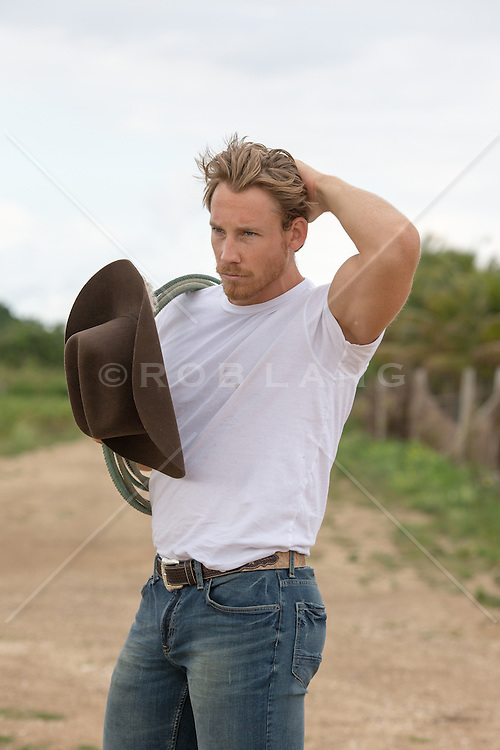 cowboy holding his cowboy hat outdoors on a dirt road
