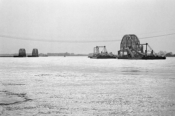 Nederland, Nijmegen, 7-5-1983Vervanging van de oude spoorbrug, die uit drie aparte bogen bestond, door een enkelvoudige overspanning van 235 meter, dan de grootste van ons land, waarbij een  oud brugdeel wordt vervangen door een betonnen aanloopbrug. De nieuwe brug is in 2004 uitgebreid met een fietsbaan, de zgn. snelbinder. Links op de foto worden de twee oude brugdelen weggevaren, recht de nieuwe brug die de volgende dag geplaatst wordt.Foto: Flip Franssen/Hollandse Hoogte