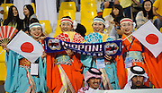 Local arab men from Qatar watch the game amongst Japan female fans dressed in traditional dress of the Kimono