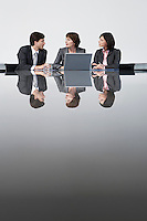 Three business colleagues using laptop at conference table