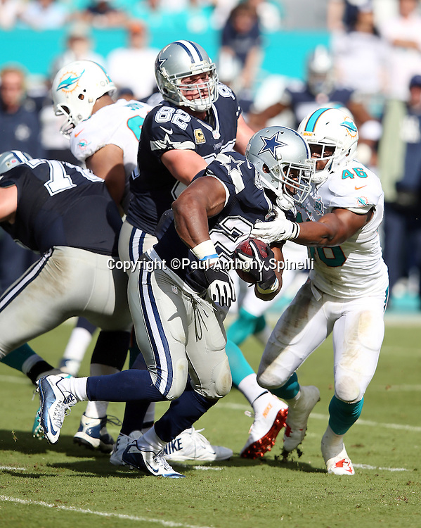Dallas Cowboys running back Robert Turbin (23) runs the ball while trying to avoid a tackle attempt by Miami Dolphins linebacker Neville Hewitt (46) during the 2015 week 11 regular season NFL football game against the Miami Dolphins on Sunday, Nov. 22, 2015 in Miami. The Cowboys won the game 24-14. (©Paul Anthony Spinelli)
