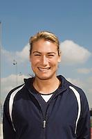 Female track athlete standing on track, portrait