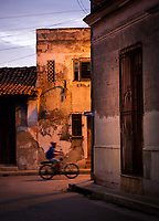 CAMAGUEY, CUBA - CIRCA JANUARY 2020: Boy riding a bicycle in the streets of Camaguey