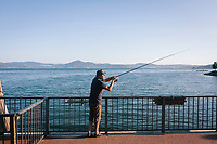 ANGUILLARA SABAZIA (LAKE BRACCIANO), ITALY - 26 JULY 2017: Fisherman Mauro Noro, 42, fishes from a jetty in Lake Bracciano, whose level has dropped more than 1,50 meters, in Anguillara Sabazia (Lake Bracciano), Italy, on July 26th 2017.<br /> <br /> Lake Bracciano provides eight percent of Rome's water and has sunk about 1.5 meters<br /> <br /> A severe drought and sweltering temperatures have led Rome city officials to consider a potential rationing of drinking water for eight hours a day for a million and a half Rome residents. The water crisis has become yet another sign of man being at the mercy of an increasingly extreme climate, but also of once mighty Rome's political impotence, managerial ineptitude and overall decline.