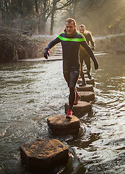 © Licensed to London News Pictures. 22/01/2017. Dorking, UK. Two soaking wet runners cross the stepping stones over the River Mole after taking a dip in the near freezing waters as part of a training programme near Dorking after another night of below freezing temperatures.  Photo credit: Peter Macdiarmid/LNP