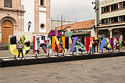 People pose in front of giant letters at Plaza Morelos in Uruapan, Michoacan, Mexico.