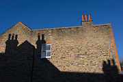The shadow of a neighbour's chimneys on the side of an end-of-terrace house in south London, on 30th January 2019, in Herne Hill, Lambeth, London, England.