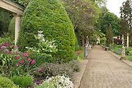 A gravel path surrounded by topiary and statues in the Peto Garden at Iford Manor in Bradford-on-Avon, Wilthire