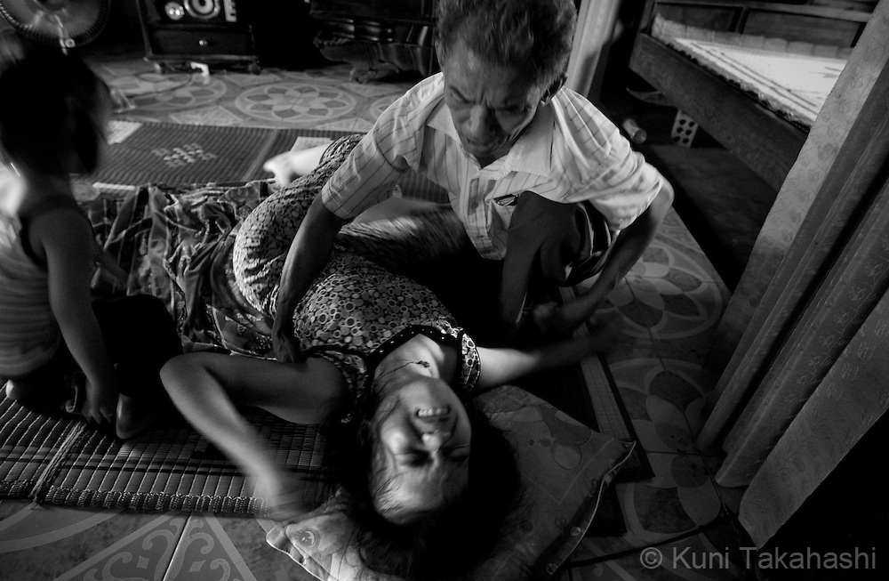 Do Thi Hang, 19, suffers a seizure as her father Do Duc Diu, 58, tries to comfort her at their house in Quang Binh Province in northern Vietnam on June 25, 2009. Diu, who served in the army in A Shau Valley and was sprayed upon directly countless times, lost 12 of his 15 children before they turned three years old. Two of his existing daughters have health problems - one has fluid in the brain and the other has cerebral palsey-like symptoms.