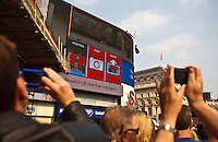 Tourists on a double decker bus tour take snapshots at Picadilly Circus, London, England.