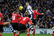 WBA's Gareth McAuley © is crowded out by Cardiff's defence as he goes for a header at goal. Barclays Premier league, Cardiff city v West Bromwich Albion at the Cardiff city Stadium in Cardiff, South Wales on Saturday 14th Dec 2013. pic by Andrew Orchard, Andrew Orchard sports photography.