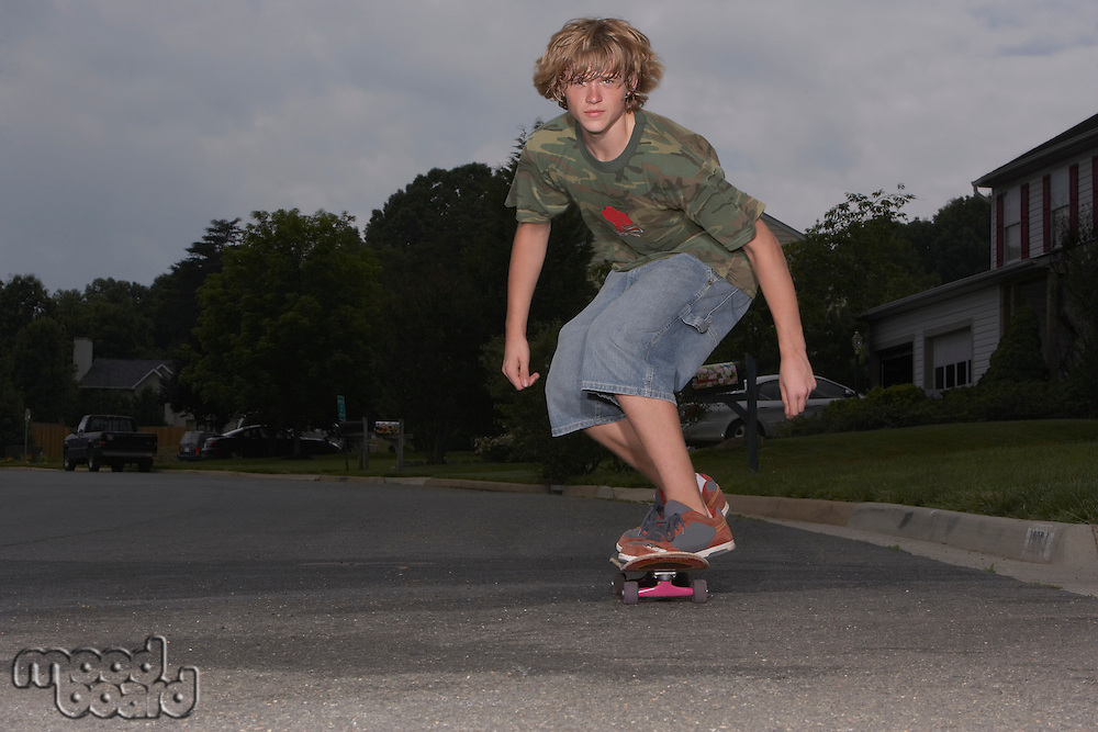 Teenage boy (16-17) skateboarding on street
