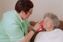 Carer assisting elderly woman by washing her face,