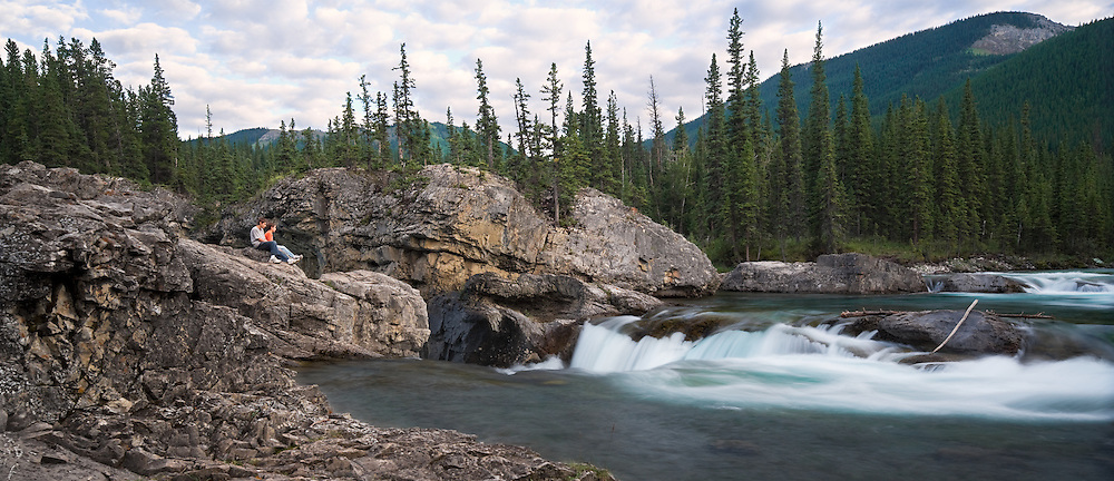 Panoramic image of Elbow Falls (Alberta).  Two boys sitting on the rocks watching the water cascade into the gorge below.  This is a 5-shot stitched image.