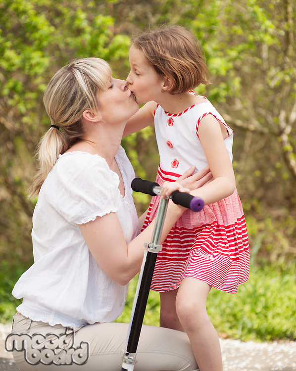 Mother and daughter kissing in park with scooter