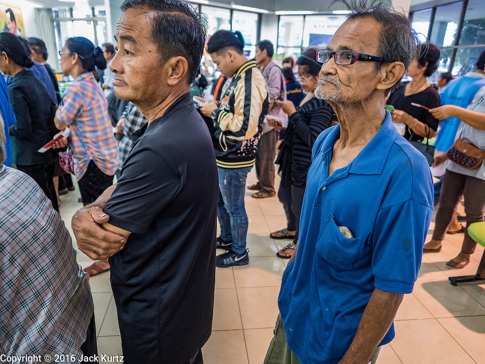 15 DECEMBER 2016 - PRACHINBURI, THAILAND:  People wait in line for their cash disbursements in a government credit union in Prachinburi, Thailand. The Thai government said people who earn 30,000 Baht (about $857 US) or less per year are entitled to a 3,000 Baht cash payment (about $85.7 US) and those who earn 30,000 Baht to 100,000 Baht (about $2,857 US) per year are entitled to a 1,500 Baht (about $42.8 US) cash payment. The plan is meant to help low income people, especially the rural poor. Government banks in rural areas offering the disbursement have been crowded with people seeking their payments this week.      PHOTO BY JACK KURTZ   Social Safety Net