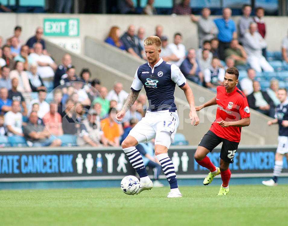 Byron Webster of Millwall plays the ball under pressure from Jacob Murphy of Coventry City during the Sky Bet League 1 match between Millwall and Coventry City at The Den, London, England on 15 August 2015. Photo by Edmund  Boyden.