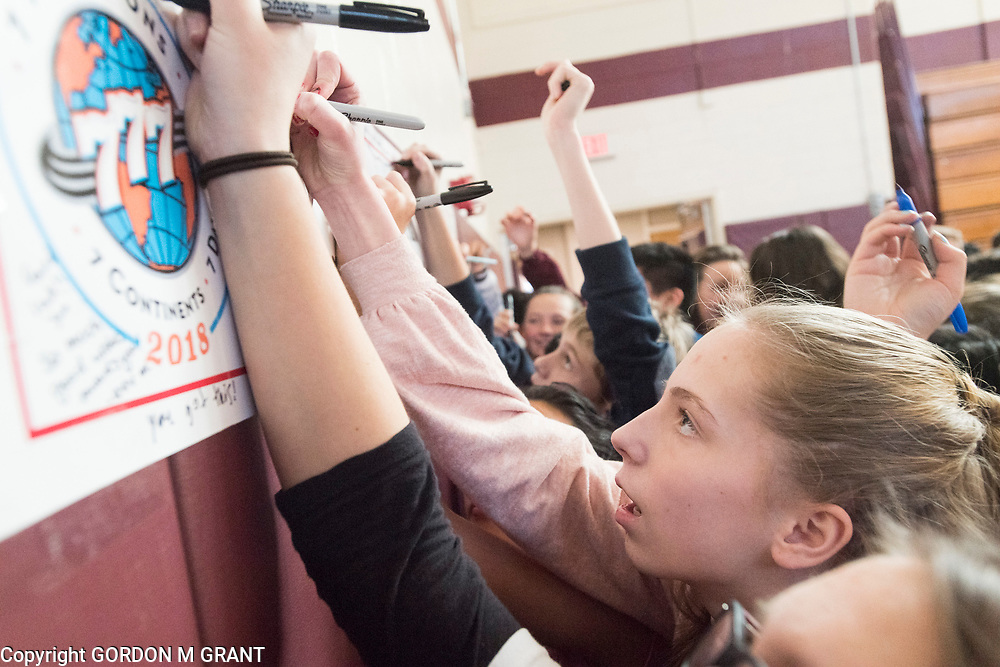 Jane Brierley, 12, a 7th grade student at the East Hampton Middle School, signs a poster during a sendoff in honor of social studies teacher Cara Nelson, at the school in East Hampton, Jan. 18, 2018. Nelson will leave next week to participate in a trip where she will run seven marathons in seven days on seven continents.