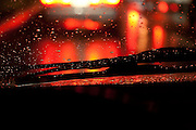 night shot thru a car windshield with raindrops of a wet street with bright red reflections